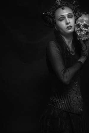 Horned lady with skull posing over dark background