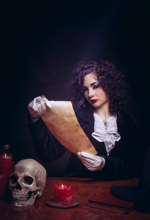 Young lady reading the scroll over dark background