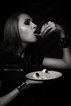 Gothic girl posing with her halloween dinner