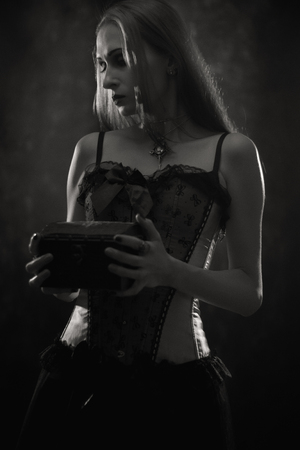 Sad gothic girl with chest posing over dark background