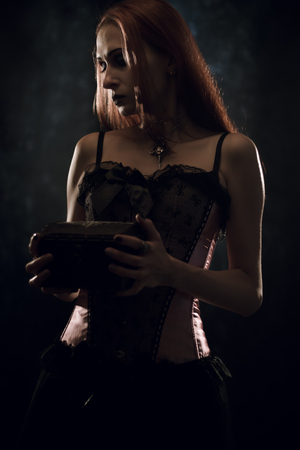 Sad gothic girl posing with chest over dark background