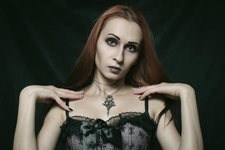 Beautiful gothic girl in corset posing over dark background