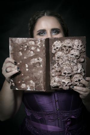 Girl with Necronomicon posing over dark background