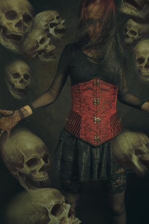 Gotisches Mädchen im roten Korsett, das eine Horde von Schädeln beschwört