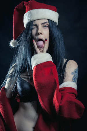 Sexy brunette girl in Santa's costume showing her tongue over dark background 스톡 콘텐츠 - 120790695