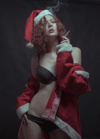Seductive girl in Santa's costume smoking over dark background 免版税图像