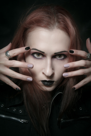 Gothic girl in dark clothes posing over dark background