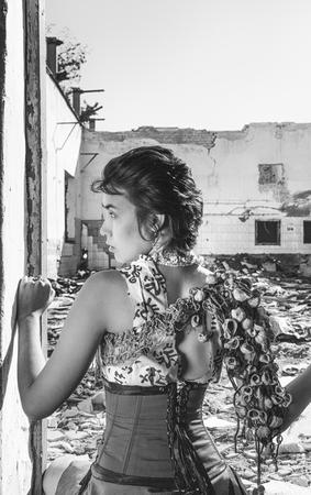 Beautiful post apocalyptic girl with seashells on her shoulder posing over ruins