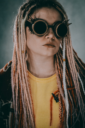 Cyberpunk girl with goggles posing over grey background Stock Photo