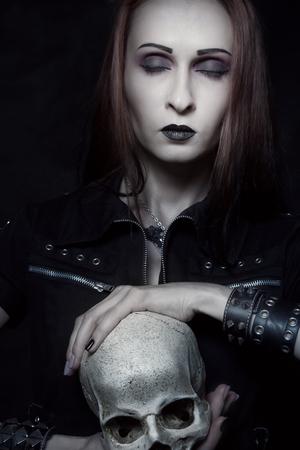 Heavy metal girl with skull posing over dark background Imagens - 120791020