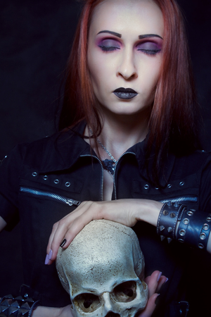 Heavy metal girl with skull posing over dark background