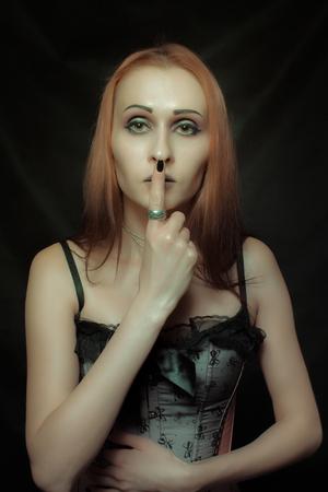 Gothic girl posing over dark background
