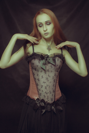 Beautiful redhead gothic girl posing over dark background