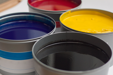 Cmyk color paints in cans over white