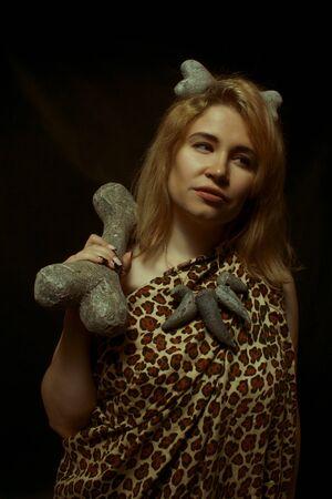 Prehistoric woman posing over dark background with huge bone Stock Photo