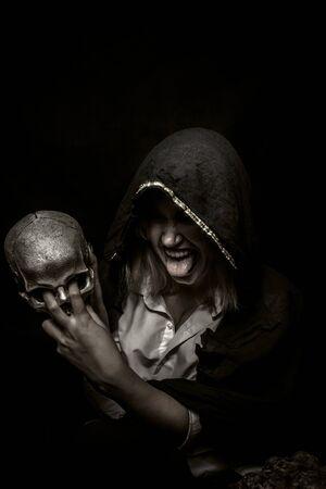 Chamán loco con calavera posando sobre fondo oscuro Foto de archivo