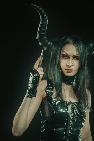 Seductive horned gothic girl in latex with knife.