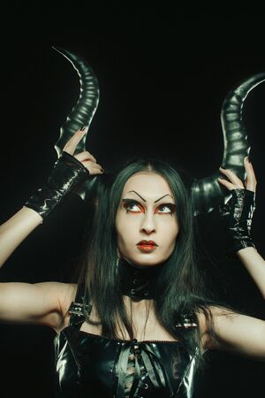 Seductive girl in latex touching her horns over dark