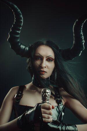 Horned seductive demonic girl posing with sword over dark