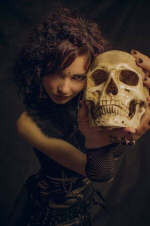 Fashionable  witch with skull posing over dark