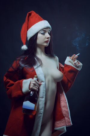 Naked Santa's helper posing with cigarette and wine over dark background
