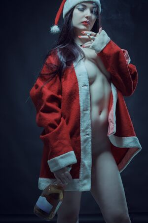 Naked Santa's helper posing with cigarette and wine over dark background 免版税图像