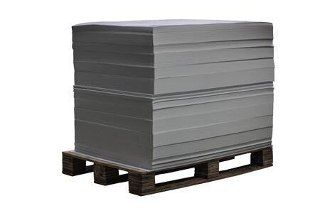 Pallet with blank offset paper standing in a printing house. Isolated over white.