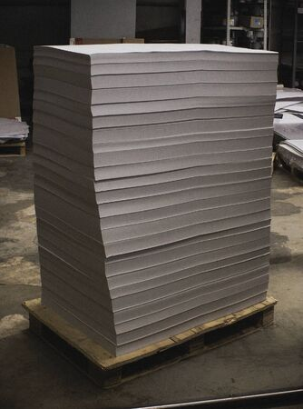 Pallet with blank offset paper in printing house. Offset, industry.