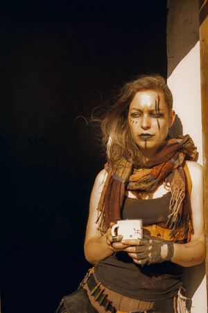 Lonely sad postapocalyptic girl with a cup