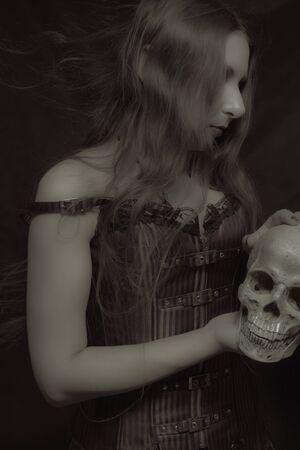 Gothic girl with skull posing over dark background