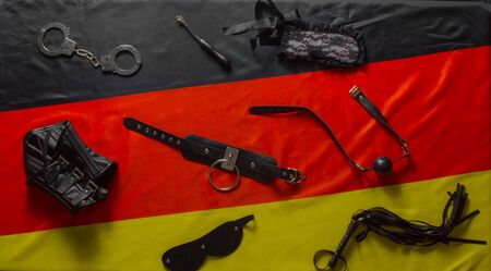 Bdsm stuff laying over german flag.  Deviant sexual behaviour and role playing concept.