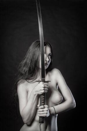 Naked woman with katana posing over dark