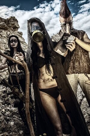 Girl in hood and gasmask posing with two raiders amongst wasteland Foto de archivo