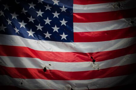 Closeup of grunged aged American flag over dark background