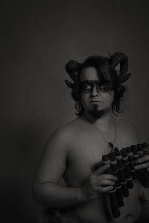 Horned faun posingwith wooden panflute 写真素材