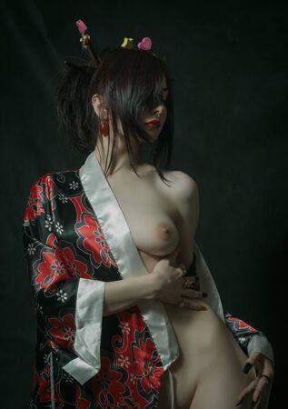 Pretty naked  geisha posing over dark