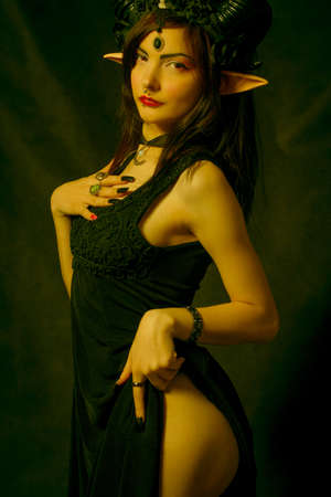 Seductive horned girl with elvish ears posing over dark background