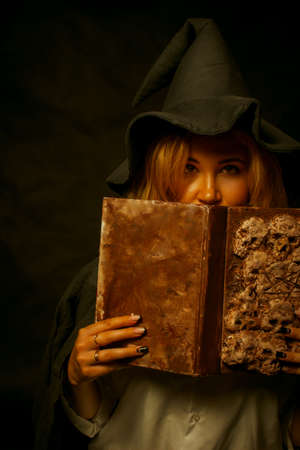 Cute witch posing over dark background with spell book