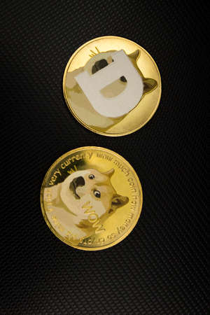 Dogecoin cryptocurrencies laying on a laptop in soft light