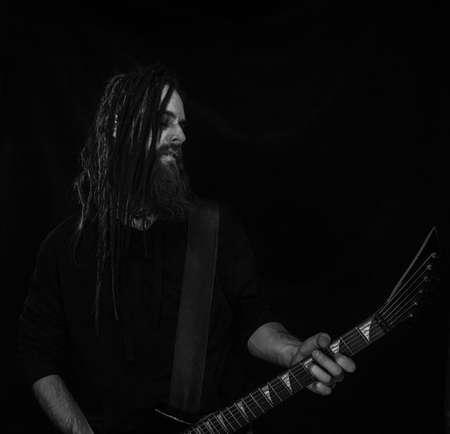 Brutal guitarist with black guitar over dark Standard-Bild