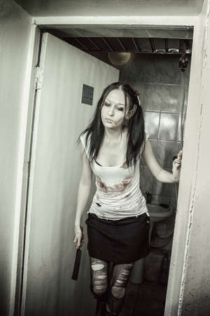Seductive young gothic girl with bloody chopper and lollipop