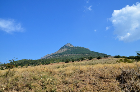 Lonely mountain against a blue cloudy sky.
