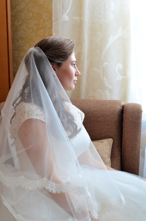 marriageable: Bride in veil sitting in the chair sideways.