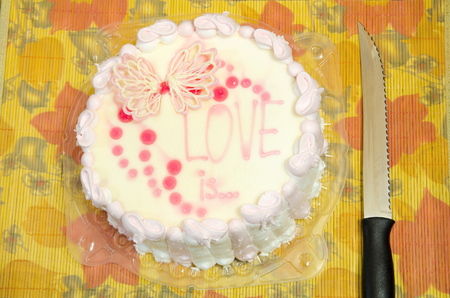 butterfly knife: White sweet cake with LOVE is inscription and serrated knife. Stock Photo