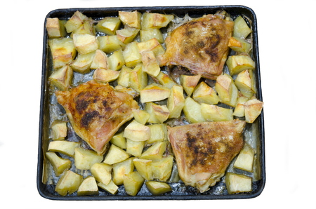 seizing: Three fried chicken thighs lie on a baking tray with cut potatoes. Stock Photo