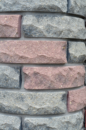 Cladding of a rounded facing texture bricks of two colors with an oblique offset.