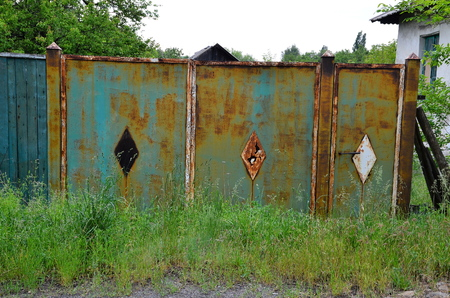 Old rusty gates of an abandoned house.