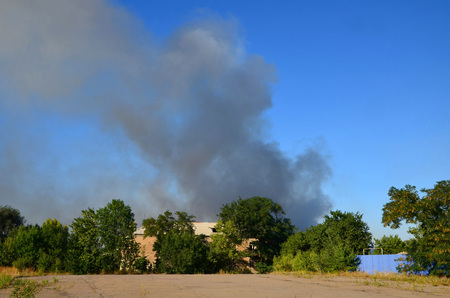 Clubs of smoke are visible because of a two-story house.