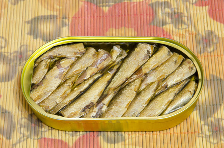 Open metal can with sprats in oil. Stock fotó