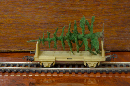 A toy railway car loaded with an artificial Christmas tree. Stock Photo